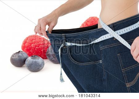 Digital composite of Midsetion of woman wearing loose jeans with fruits in background