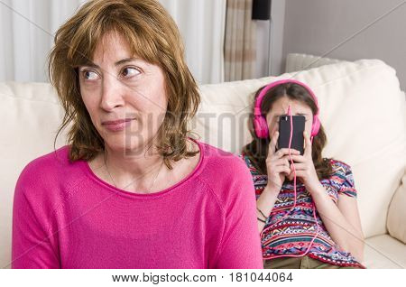 Mother Are Angry With Her Daughter. Teen Girl With Pink Headphones Is Listening Music With Her Phone