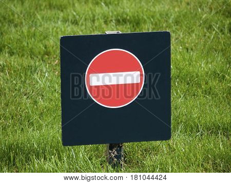 No entry warning sign in a grass field