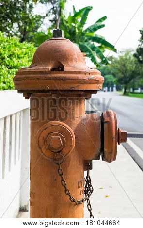 A side view of antique fire hydrant connection on the footpath with low concrete fence background.