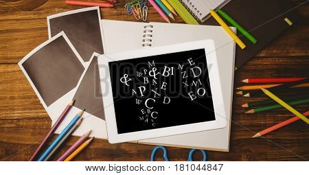 Digital composite of Overhead view of letters in digital tablet with photographs and color pencils on wooden table
