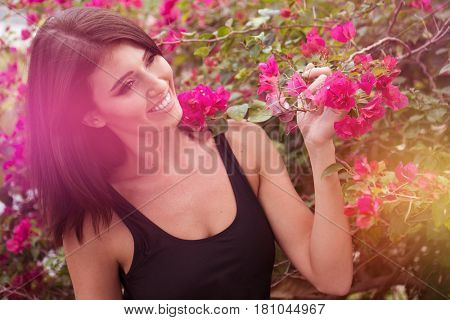 Fashion style beauty romantic portrait of young beautiful woman  in black swimsuit posing between pink flowers