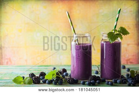 Fresh blackberry and blueberry smoothie in glass bottles with  straws