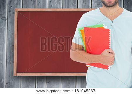 Digital composite of Midsection of male college student holding books while standing against notice board