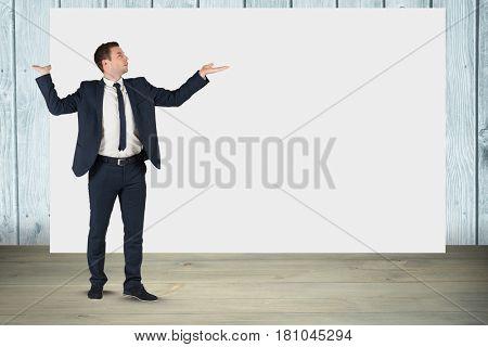 Digital composite of Businessman gesturing while standing against blank billboard