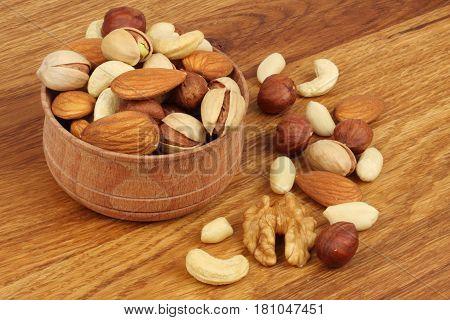mix almonds, cashew nuts, hazelnut, peanuts, walnuts, pistachio in wood plate on wood background
