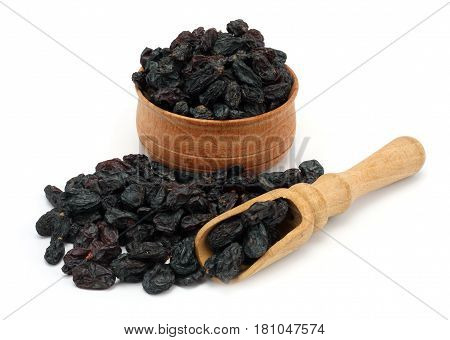 Organic dried Raisins in wood plate isolated on white background
