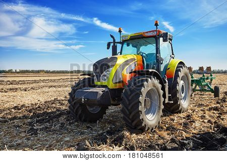 Tractor working in a field, agricultural machinery in the work, machine cultivates the land, tractor in the background cloudy sky