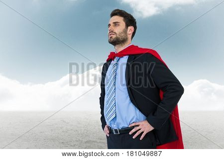 Digital composite of Businessman wearing cape while standing against sky