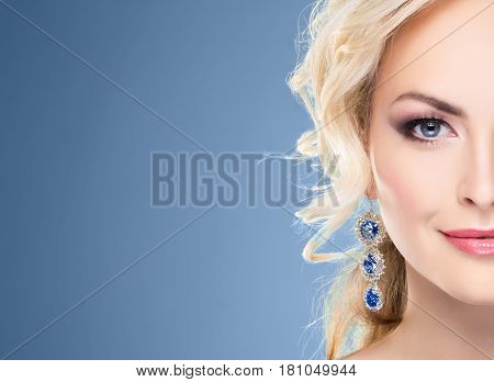 Half part portrait. Beautiful blond girl with luxury golden necklace over blue background.