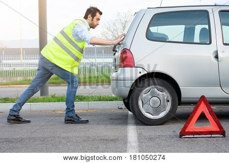 Man Pushing His Car After Engine Breakdown