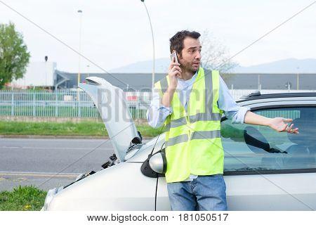 Man Calling Mechanic After Car Breakdown