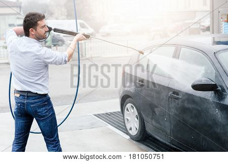 Man washing his car in a self-service car wash station
