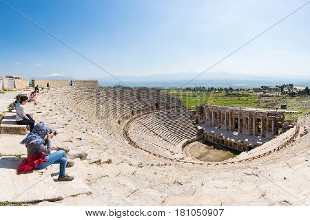 PAMUKKALE TURKEY - April 16: Tourists watching the ancient theater of the Roman city of Hierapolis on April 16 2014 in Pamukkale Turkey. The site is a UNESCO World Heritage site