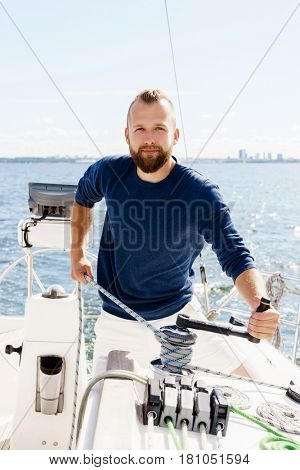 Handsome, bearded guy winding a rope on a yacht. Traveling, vacation, holiday, concept.