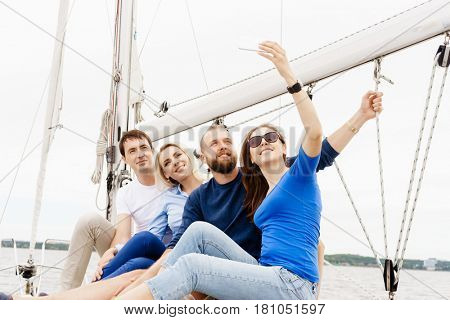 Group of happy friends traveling on a yacht and taking selfie. Tourism, vacation, holiday, concept.