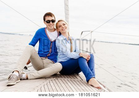 Happy and beautiful young couple sitting on deck and having a good time together. Traveling, tourism, journey, concept.