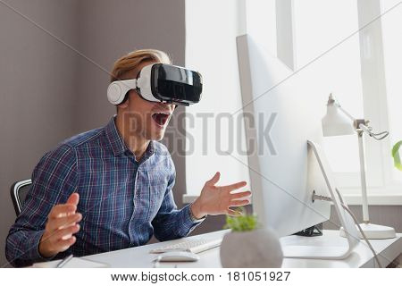 Young excited man in VR headset sitting by desktop with laptop.