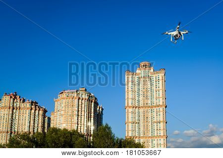 Drone quad copter with onboard high resolution digital camera flying on the city background