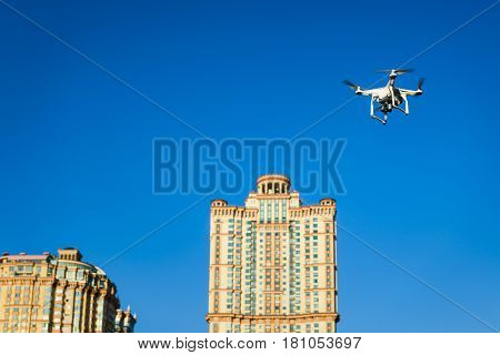 Drone quad copter with onboard high resolution digital camera flying on the city background in the blue sky