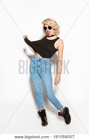 Young stylish rebel girl in sunglasses and casual outfit posing on white backgr