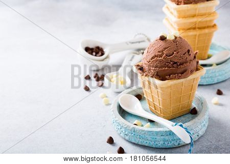 Waffle cups with chocolate ice cream, milk and white chocolate granules in measuring spoons on gray stone background. Healthy summer food concept with copy space.