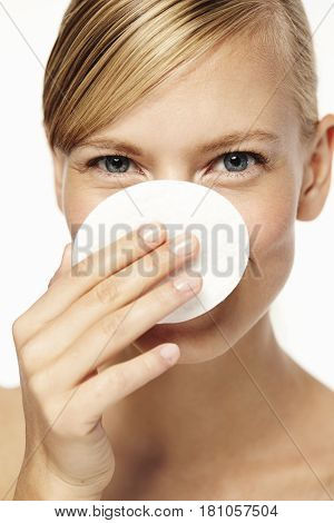 Woman holding cotton pad in front of face portrait