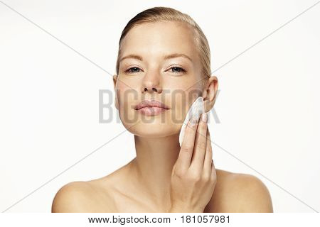 Stunning blond woman cleansing skin portrait studio
