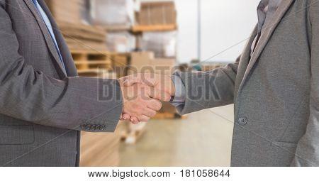 Digital composite of Midsection of businessmen doing handshake in warehouse