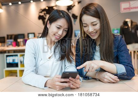 Happy women looking at mobile phone together
