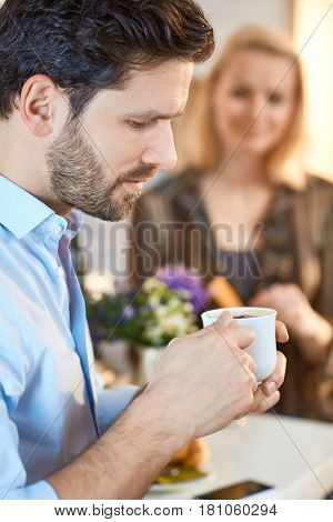 Profile of young man holding coffee cup.