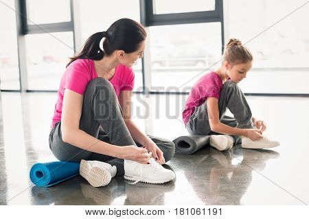 Mother And Daughter In Pink Shirts And Sneakers Tying Shoelaces In Gym