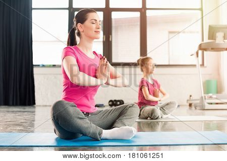 Mother And Daughter In Pink Shirts Sitting In Lotos Pose In Gym