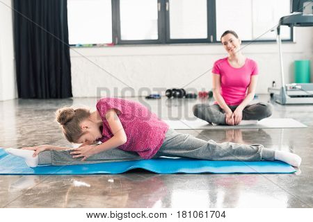 Adorable Daughter In Pink Shirts Stretching With Mother In Lotos Pose Behind In Gym