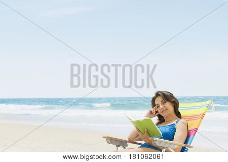 Hispanic woman reading at beach