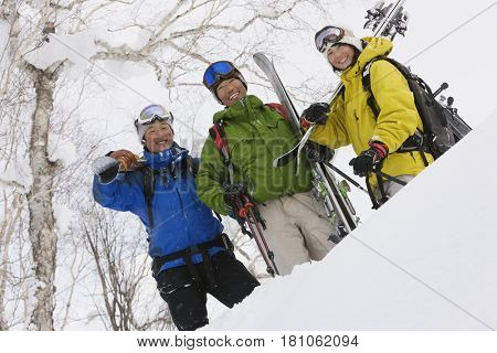 Asian friends holding skis in snow