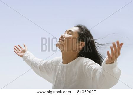 Asian woman with hands outstretched
