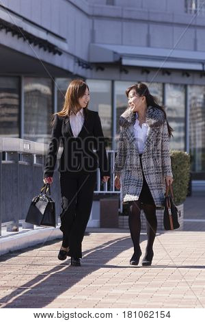 Asian businesswomen walking outdoors