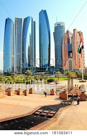 ABU DHABI UAE - JANUARY 26 2017: Etihad Towers buildings in Abu Dhabi United Arab Emirates. Skyscrapers flag of UAE and fountain in front of Emirates Palace Hotel. Vertical view in sunny day.