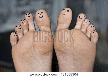 Smiley faces drawn on human toes with black pen.