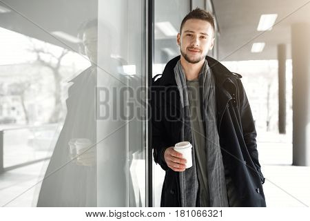 Nice guy in cool spring clothes relaxing while drinking cooffee outside, looking at camera.