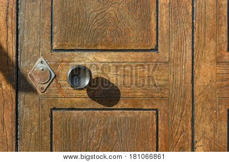 Closeup of old-fashioned round metal doorknob and keyholes on wooden door