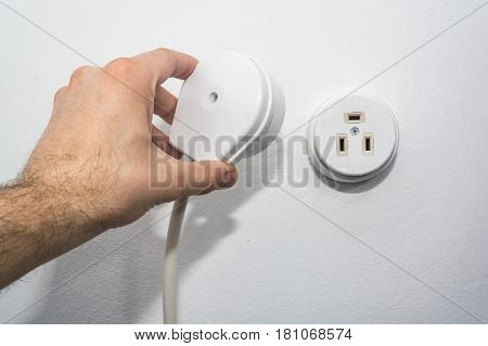 Close-up shot of male hand putting plug into socket