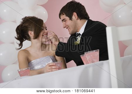 Hispanic man touching girlfriend's nose at prom