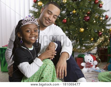 African father and daughter in front of Christmas tree