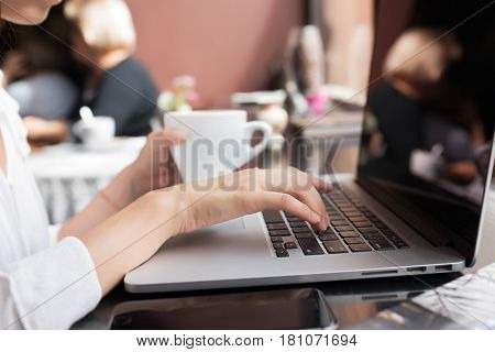 Rear view of a creative female freelancer sitting front laptop. internet
