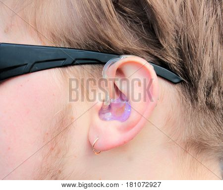 ear of a young blond man in a hearing aid