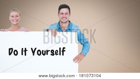 Digital composite of Smiling couple holding bill board with do it yourself text on it