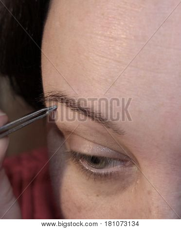 The woman removes facial hair with tweezers