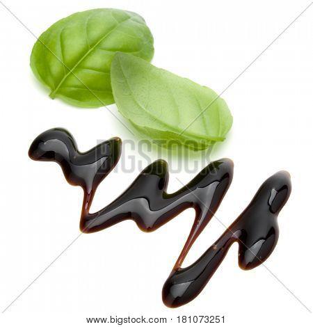 Balsamic vinegar cream and basil leaves isolated on white background. Italian salad dressing, sauce.